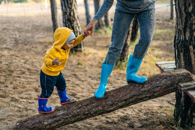 Child climbing on log while holiding mom's hand